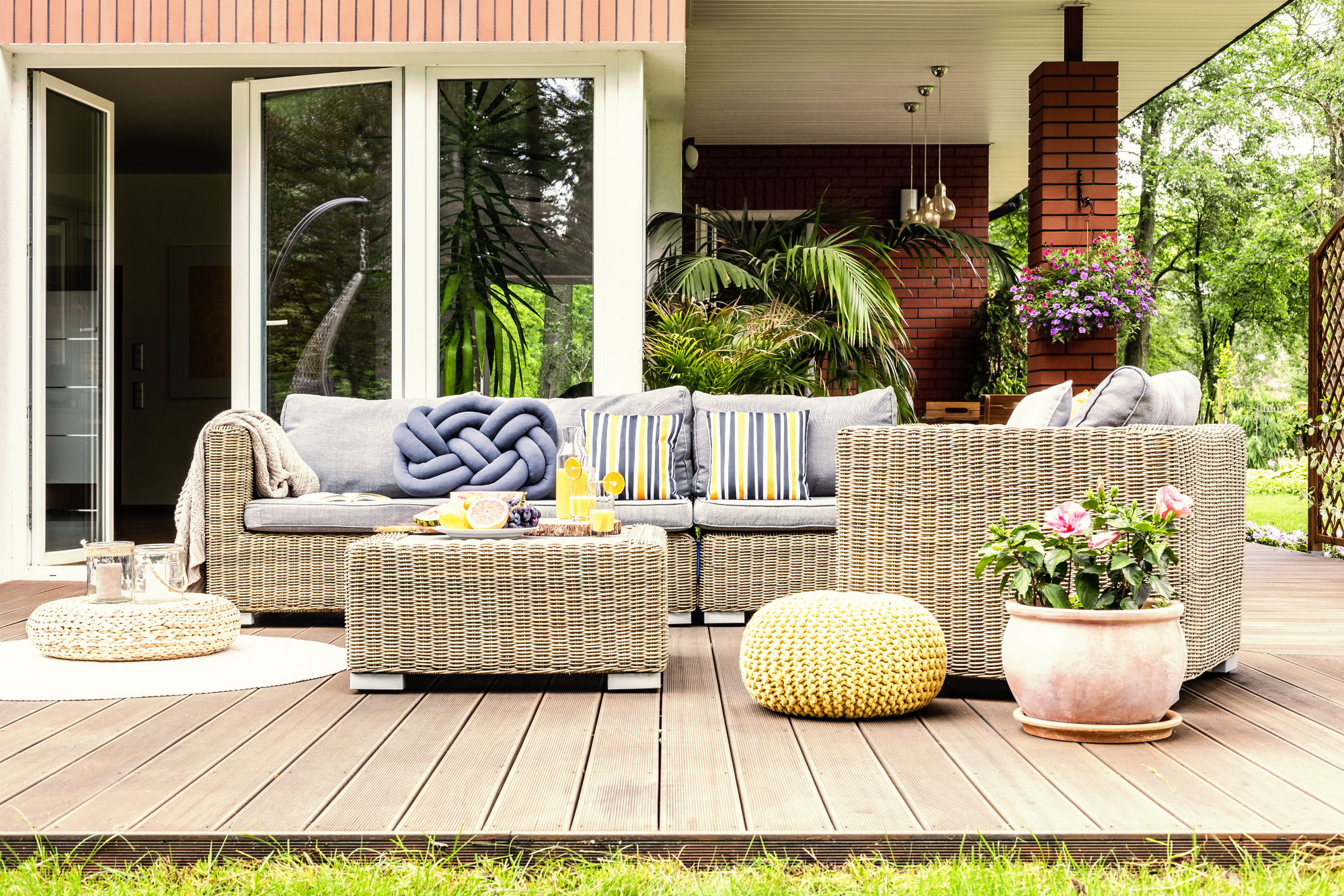 Outdoor patio seating area with big sofa and table.